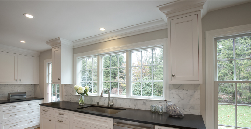 Lots of natural light due to full height windows anchor this kitchen design in Wilton CT