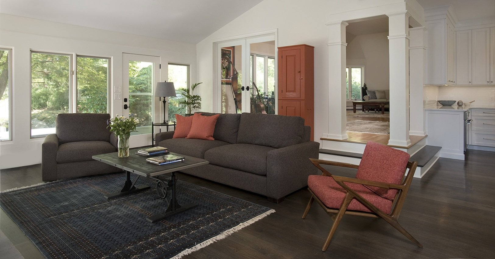 Great room with brown couches and orange chairs