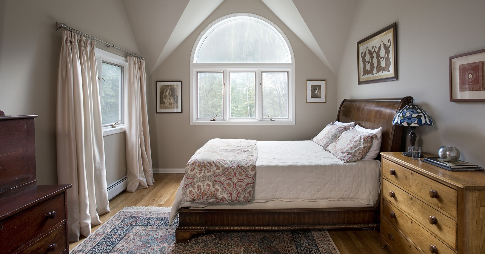 Guest bedroom with symmetrical ceiling and round top window