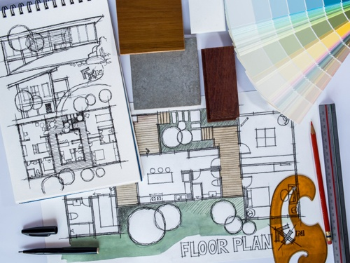 Remodeling floor plans in notebook with french curve and material selections