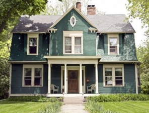 Charming antique victorian home with green shutters and cream colored siding.