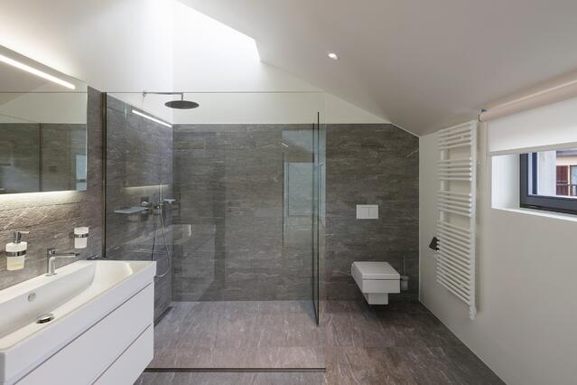 Large shower goes wall to wall, with towel warmer and glass panel.