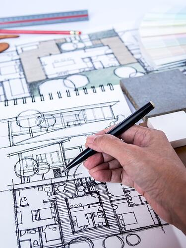 drawing architectural designs in a notebook