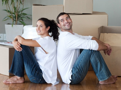 couple waiting to unpack moving boxes