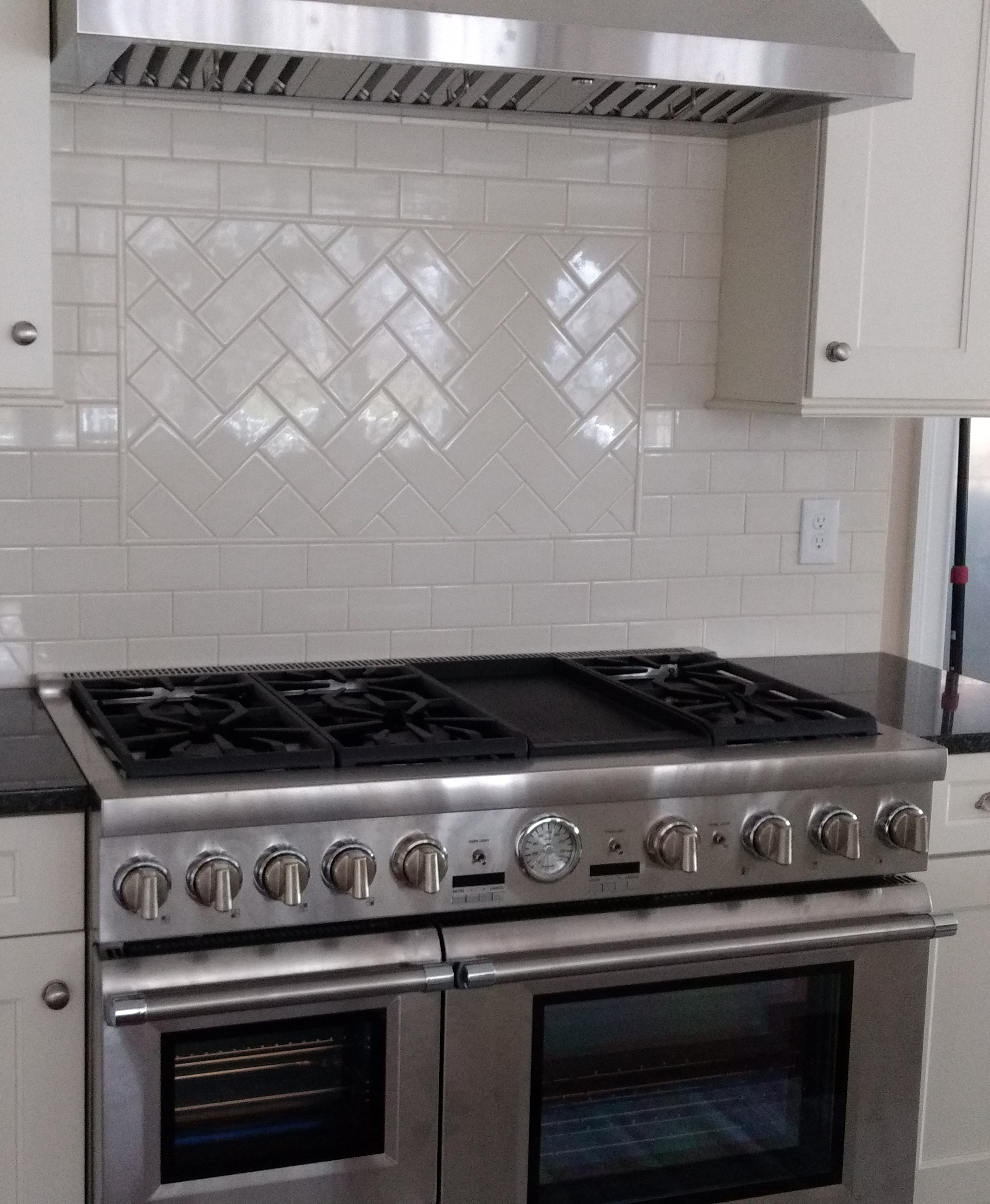 Herringbone subway tile pattern behind freshly installed stove and hood