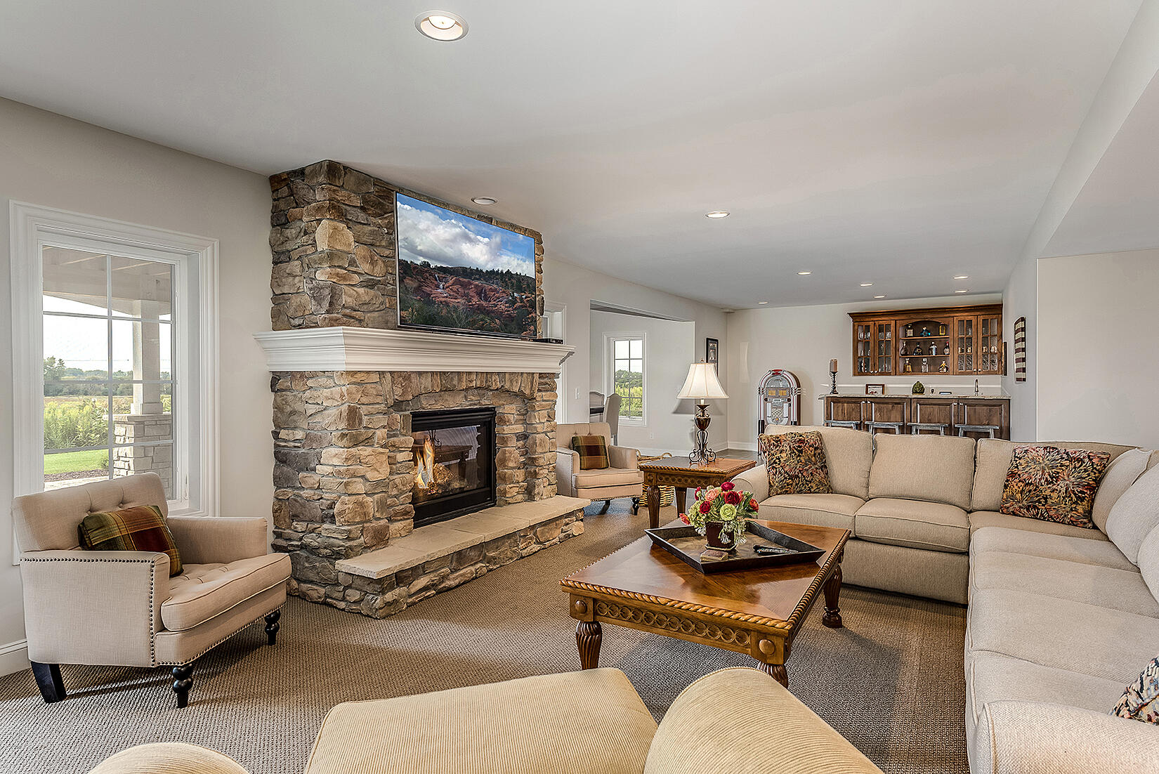 Beautiful basement remodel with fireplace and bar, perfect for the whole family.