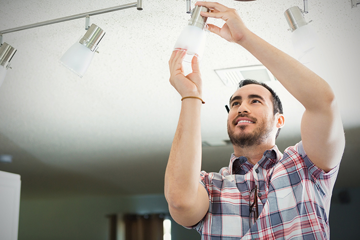 Contractor in a plaid shirt installing a light bulb - easy task for any homeowner once you know which light bulb to use.