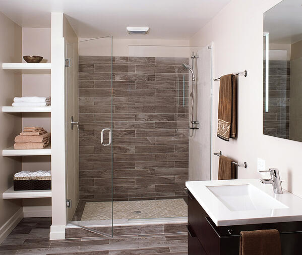 Gorgeous updated guest bath in renovated basement with full tile shower and glass doors.