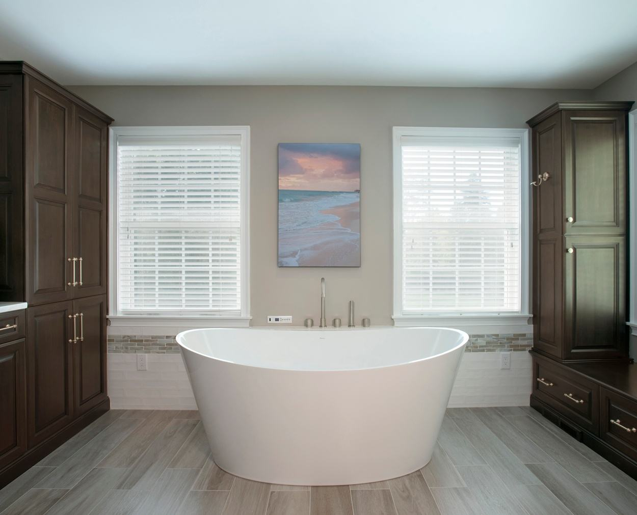 White freestanding tub with Grabill cabinets in a dark stain.