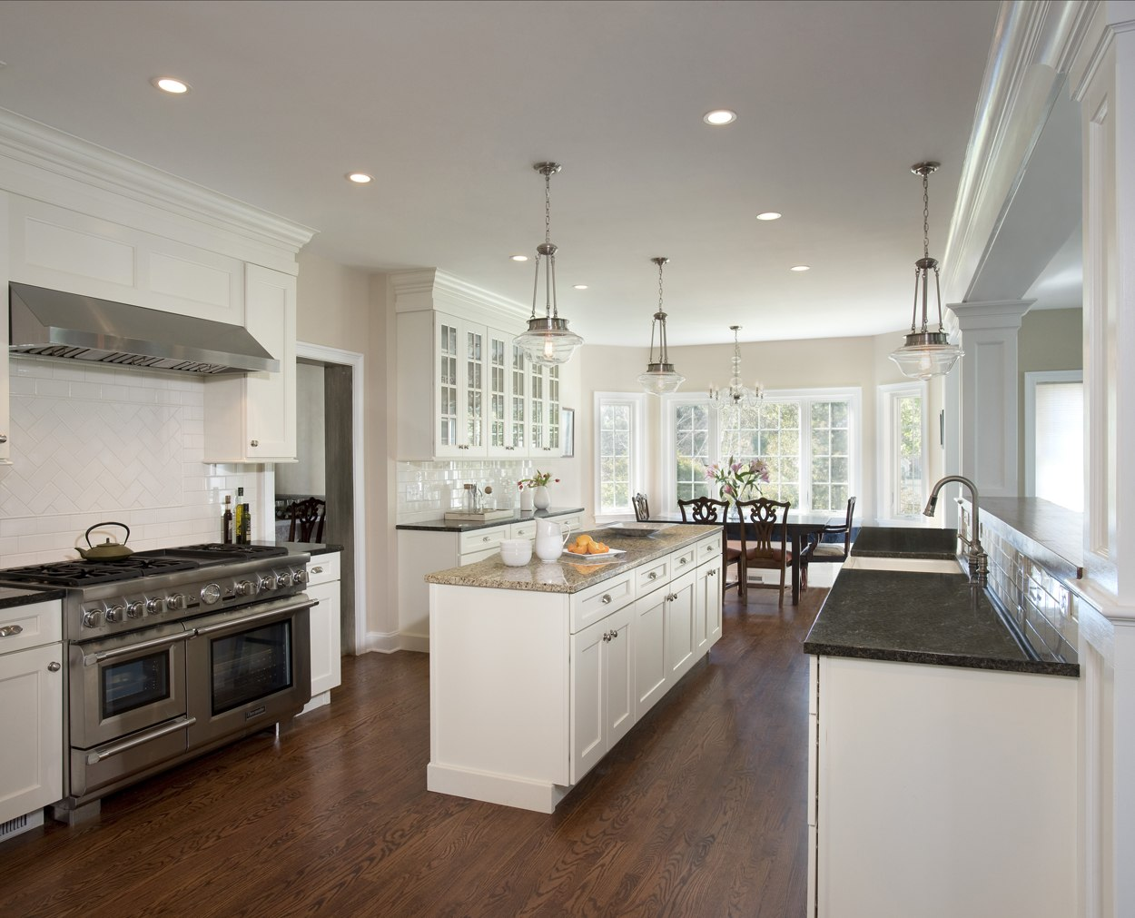White kitchen with lots of glass doored storage in Clark Construction design