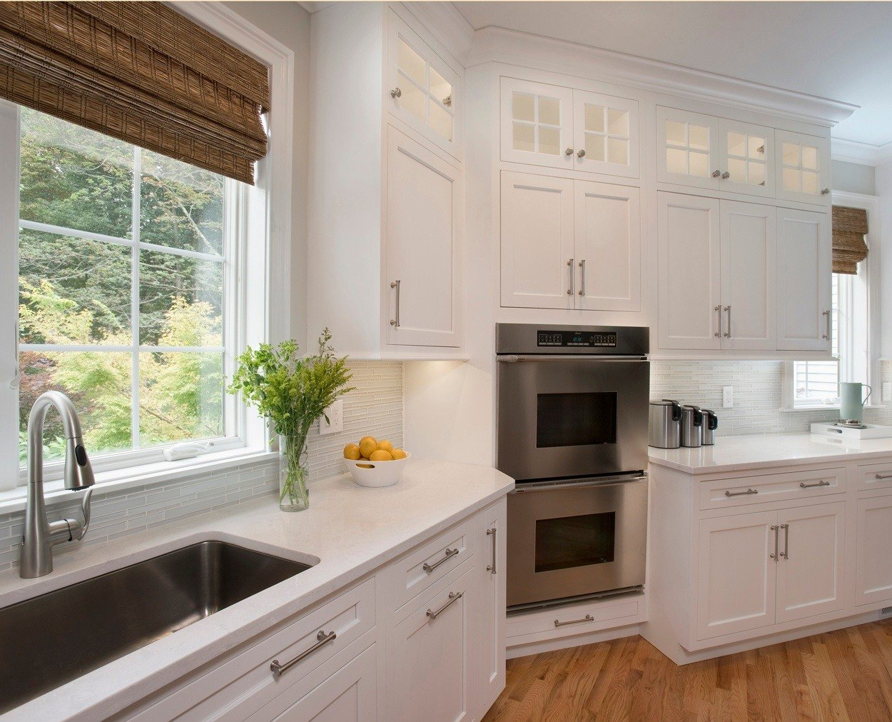 Corner cabinet houses double oven, with large sink under window.