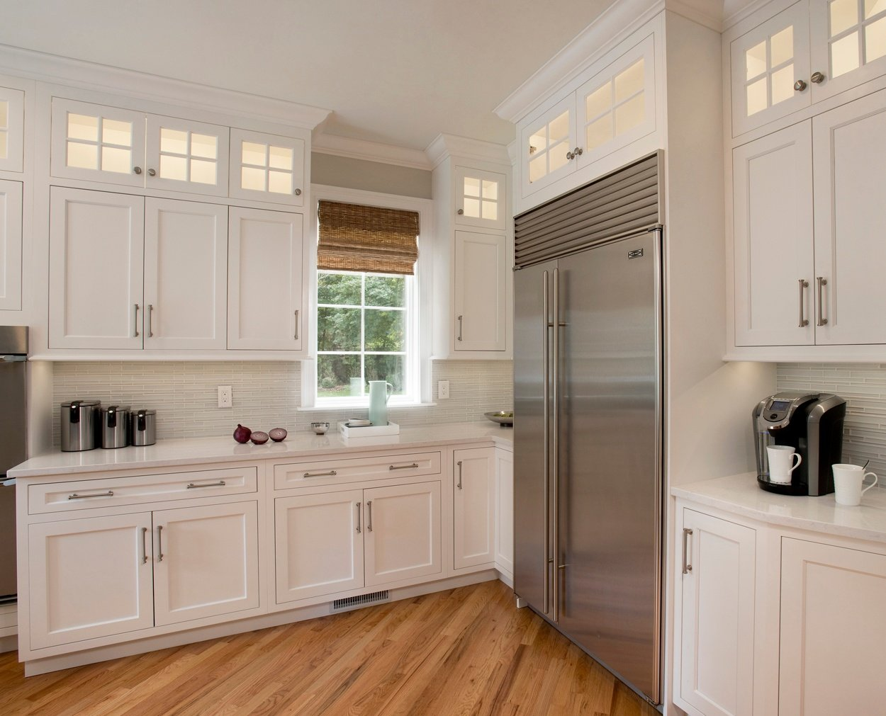 The corner of a classic white kitchen with Subzero refrigerator