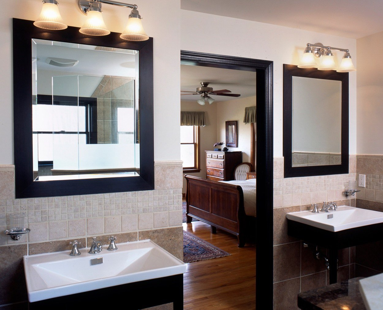 Dark framed mirrors and matching vanities in remodeled master bedroom suite.