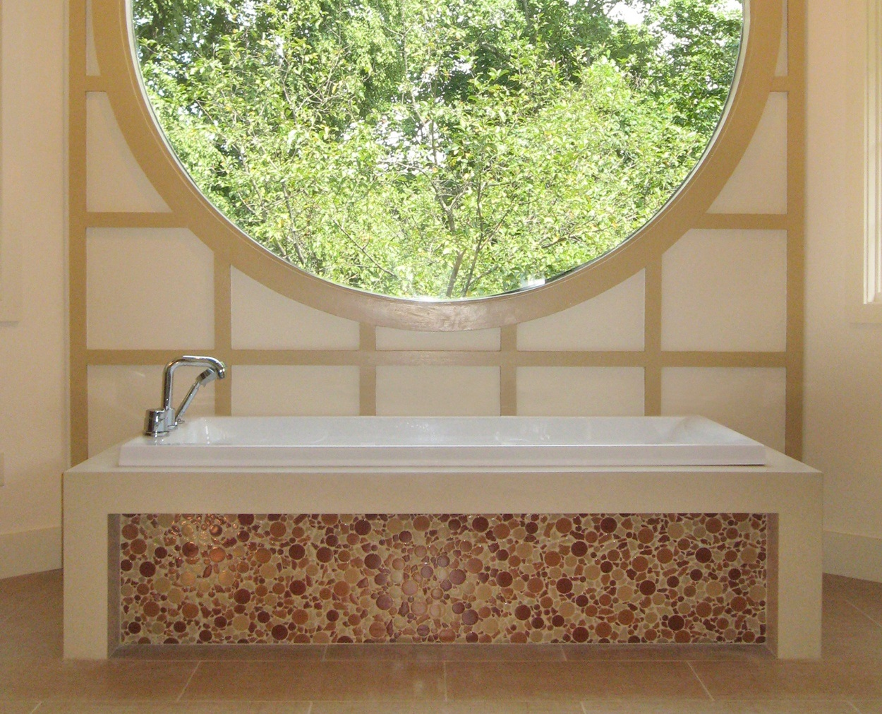 Tub deck looks like on piece of stone, with round glass tile