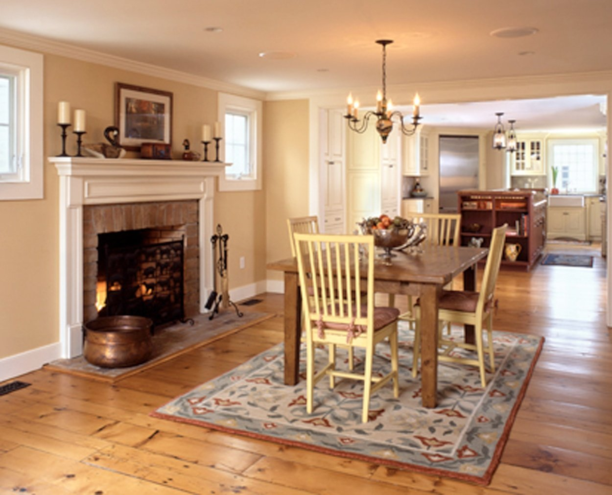 Dining table to the right of the fireplace in this traditional colonial home.