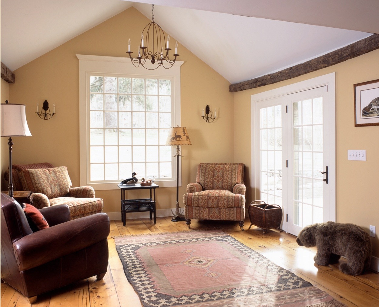 Stuffed bear in great room with large picture window and vintage beams.