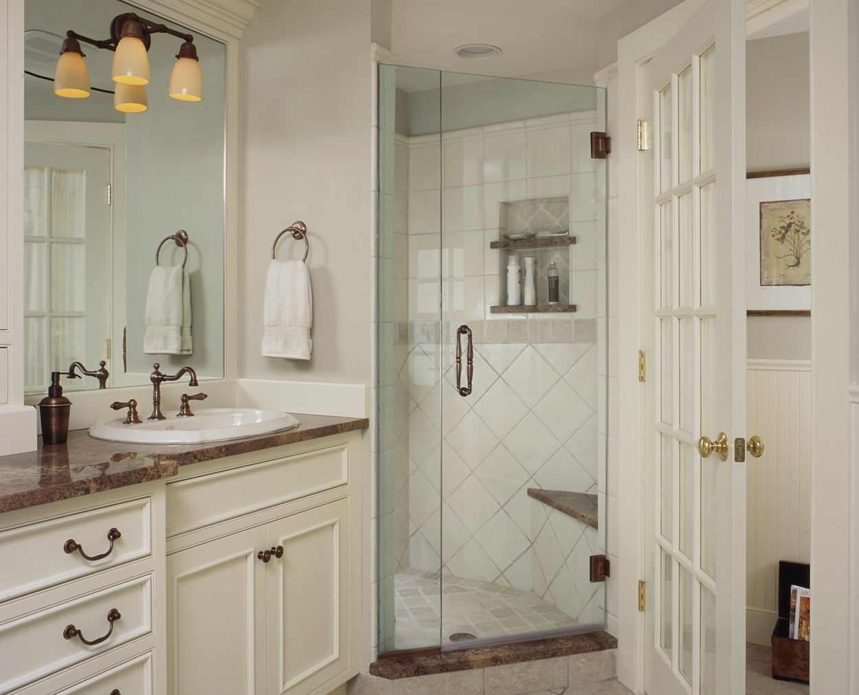 Corner frameless shower, with glass doored toilet room and traditional cabinetry.
