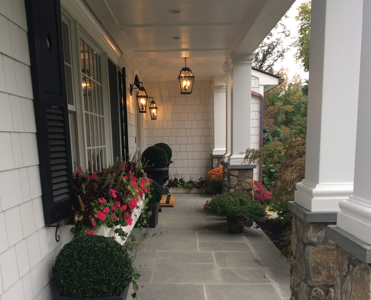 Front porch features beadboard ceiling and columns with stone bases.