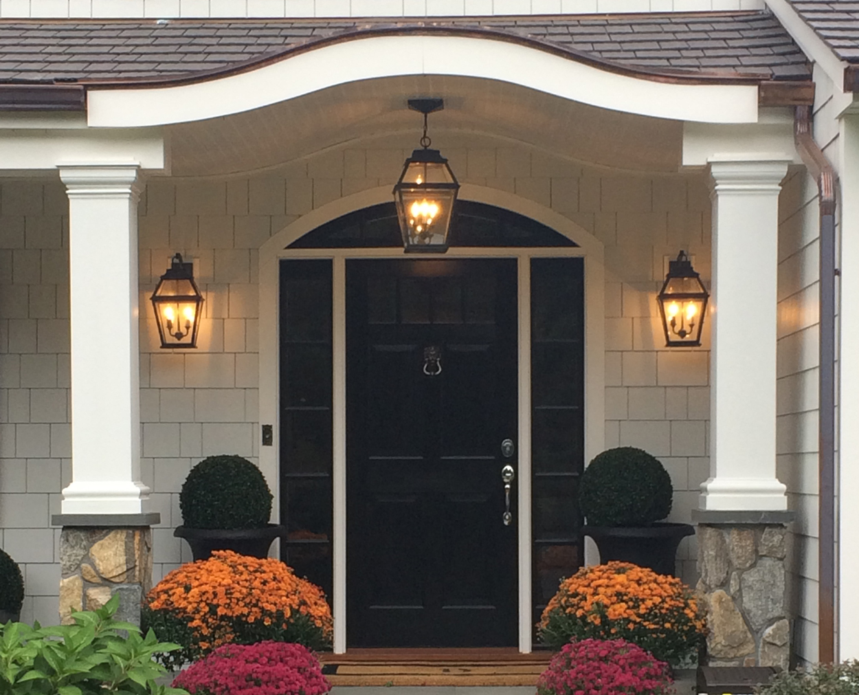 Black front door with columns and stone bases