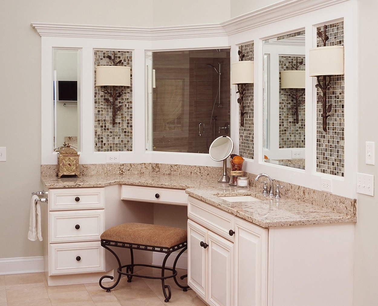 Custom cabinetry with detailing around mirrors coordinates with free standing tub details.