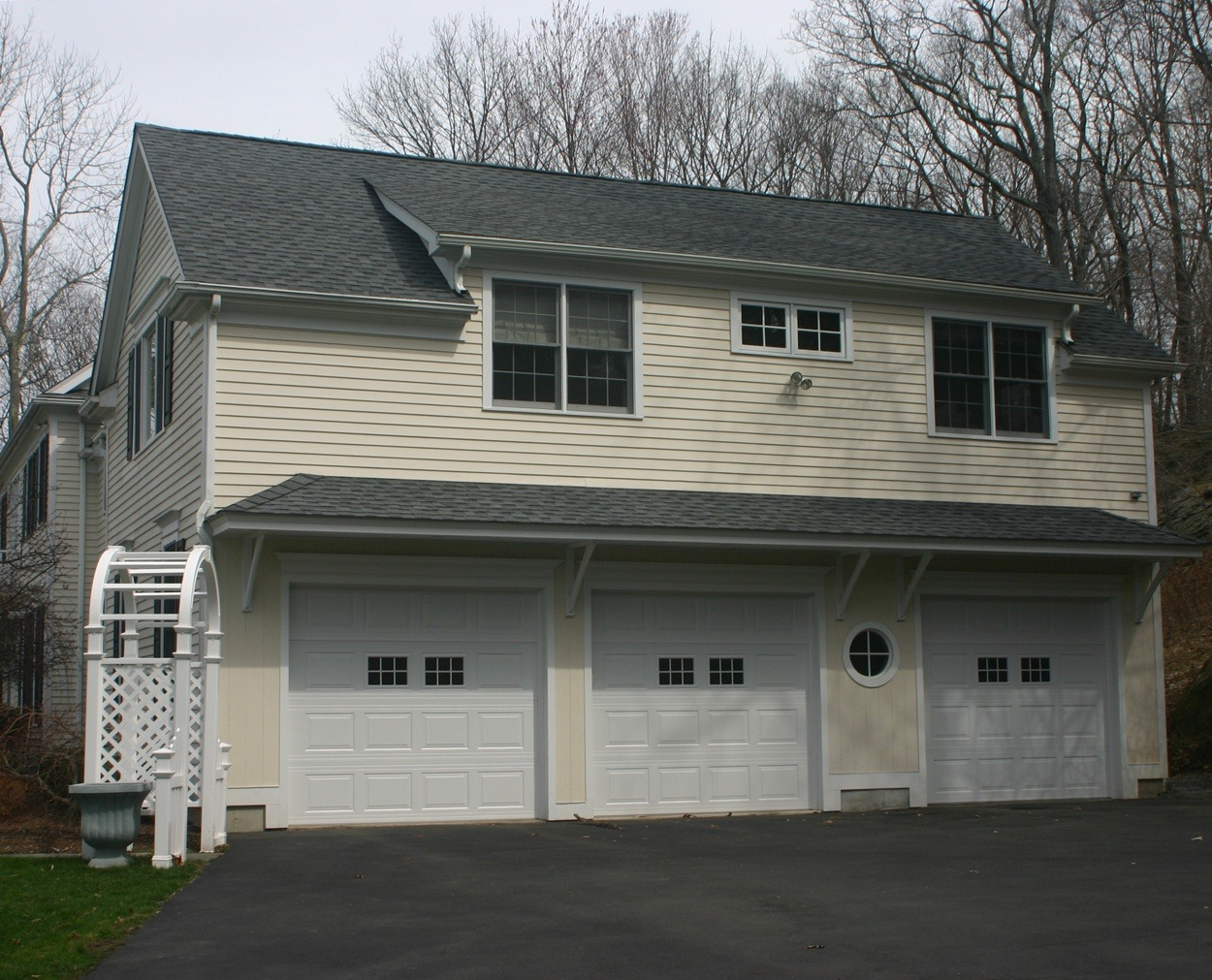 Triple bay garage with a shed dormer and interesting windows.