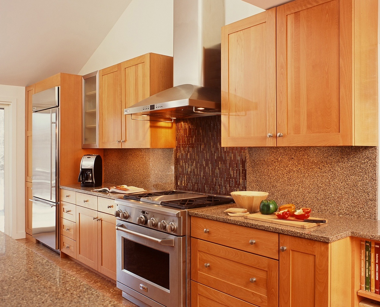 Lightly stained birch cabinets highlight this range wall in a remodeled kitchen.