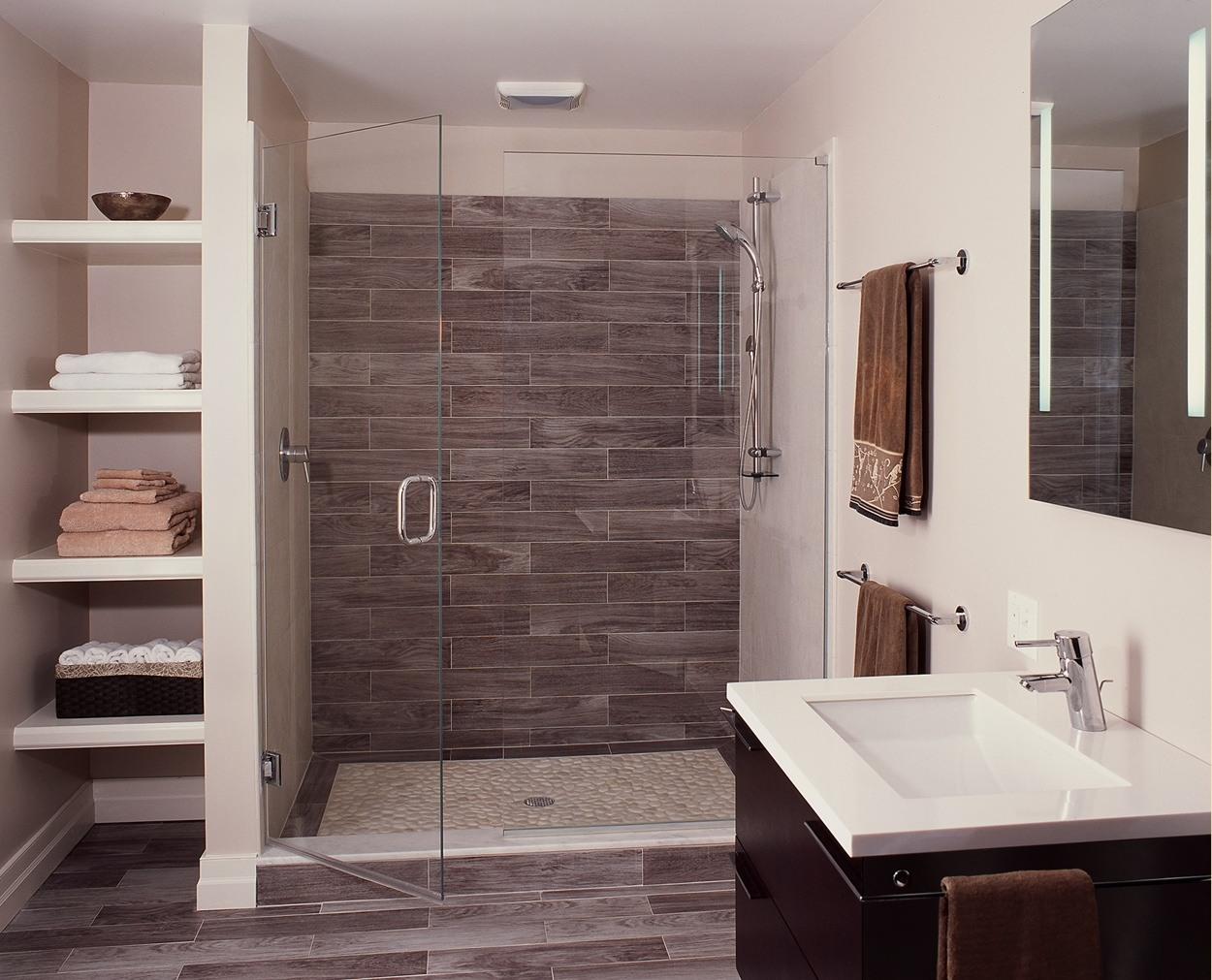 Modern bath with free standing vanity in a dark wood.